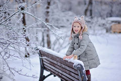 Cute happy child girl on the walk in winter snowy park Stock Images