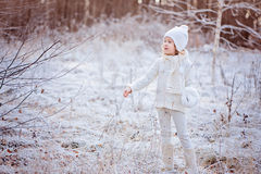 Cute happy child girl in white outfit having fun in winter snowy forest Stock Photo