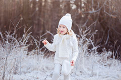 Cute happy child girl in white outfit walking in frozen winter forest Stock Photography