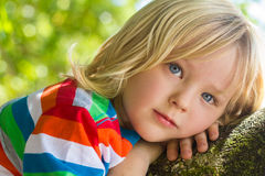 Cute, happy child relaxing deep in thought outdoors. Cute, happy child deep in thought relaxing outdoors on a tree Royalty Free Stock Images