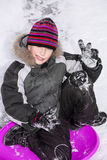 Cute happy child wearing warm clothes sledding on snow Stock Images