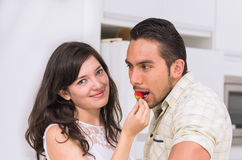 Cute happy couple feeding each other a strawberry Royalty Free Stock Image