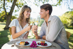 Cute happy couple sitting outside toasting with champagne with dessert Stock Photo