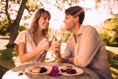 Cute happy couple sitting outside toasting with champagne with dessert Stock Photos