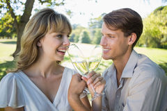 Cute happy couple sitting outside toasting with champagne Stock Photos