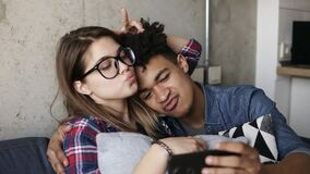 Cute happy couple taking selfies on the couch. Cute happy couple taking selfies on the couch stock video footage
