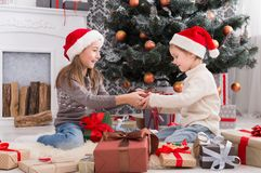 Happy children in santa hats unwrapping christmas presents Stock Photos