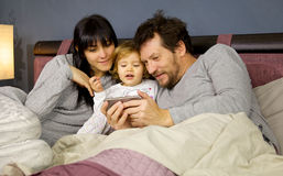 Cute happy family in bed with little daughter watching video on cell phone medium shot Stock Image