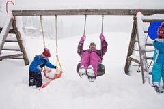 Cute happy family, having fun on the playground, swinging in win Stock Photo
