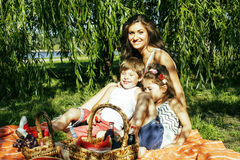 Cute happy family on picnic laying on green grass mother and kid. S, warm summer vacations close up, brother and sister together Royalty Free Stock Images