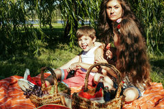 Cute happy family on picnic laying on green grass mother and kid. S, warm summer vacations close up, brother and sister together Royalty Free Stock Photo