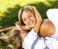 Cute happy family on picnic laying on green grass mother and kid. Warm summer vacations close up, modern people lifestyle together Stock Photo