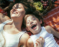 Cute happy family on picnic laying on green grass Stock Photos