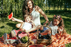 Cute happy family on picnic laying on green grass mother and kids, warm summer vacations close up, brother and sister Stock Photos