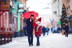 Cute happy family walking along snowy city street, winter holidays stock photography
