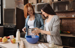 Cute happy females sifting flour. Add some ingredients. Positive delighted females wearing casual clothes sieving flour into blue plate while standing in the royalty free stock image