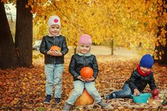 Three happy friends kids in autumn park with small pumpkins. Royalty Free Stock Photo