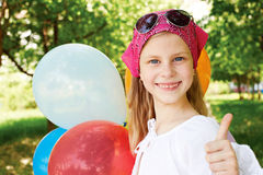 Cute Happy girl is in a amusement park with colorful balloons. Happy girl is in a amusement park with colorful balloons Stock Image
