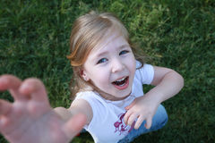 Cute happy girl with blue eyes looking up and raising her right hand in the air like superman. Supplication. Request. Stock Images
