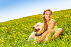 Cute happy girl cuddling dog in summer Royalty Free Stock Photography