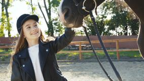 Cute girl in hat comes and caresses black mare`s head on sunny background stock video footage