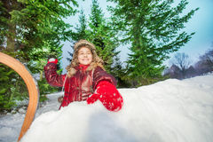 Cute happy girl holding up a snowball Royalty Free Stock Photo
