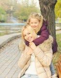 Cute happy girl hugging her mother outdoor. Stock Images