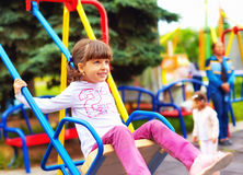 Cute happy girl, kid having fun on swings at playground Stock Photo