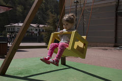 Cute happy girl, kid having fun on swings at playground. Sunny spring day Royalty Free Stock Images