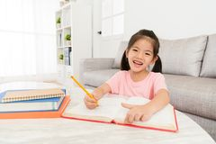 Cute happy girl kid student writing studying book. Learning knowledge preparation back to school and looking at camera smiling Royalty Free Stock Photos