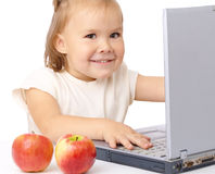 Cute happy girl with laptop and two apples Stock Photography