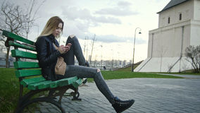 Cute happy girl with long blonde hair in leather jacket straightens  use gadget sitting on the bench Stock Photo
