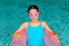 Cute happy girl in pink goggles mask in the swimming pool Stock Photos
