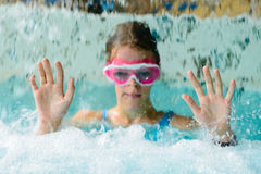 Cute happy girl in pink goggles mask in the swimming pool Royalty Free Stock Images