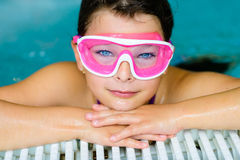 Cute happy girl in pink goggles mask in the swimming pool. Cute happy young girl child relaxing on the side of a swimming pool wearing pink goggles mask Stock Image