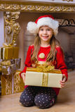 Cute happy girl in red hat holding present. Near christmas tree Royalty Free Stock Photography