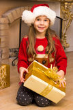 Cute happy girl in red hat holding present. Near christmas tree Royalty Free Stock Images