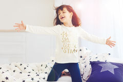 Cute happy girl singing in bedroom in the morning sun light Stock Images