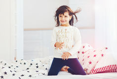 Cute happy girl singing in bedroom in the morning sun light Stock Image
