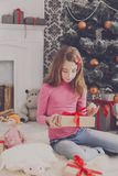 Cute girl unwrapping christmas presents Stock Photo