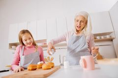 Cute happy grandmother and granddaughter enjoying cooking. Favourite hobby. Cute happy delighted grandmother and granddaughter standing in the kitchen and Royalty Free Stock Photos