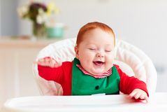 Cute happy infant baby boy in elf costume sitting in highchair Royalty Free Stock Photo