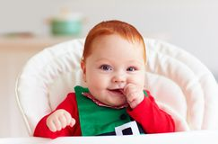 Cute happy infant baby boy in elf costume sitting in highchair Royalty Free Stock Photos