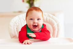 Cute happy infant baby boy in elf costume sitting in highchair Stock Photos