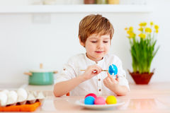 Cute happy kid, boy painting easter eggs at the kitchen desk stock photo