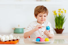Cute happy kid, boy painting easter eggs at the kitchen desk Royalty Free Stock Images