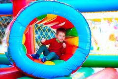 Cute happy kid, boy playing in inflatable attraction on playground Stock Photography