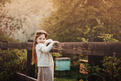 Cute happy kid girl in beige outfit climbing rustic wooden fence in spring garden Stock Photo