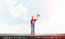 Concept of careless happy childhood with girl dreaming to become pilot royalty free stock photography
