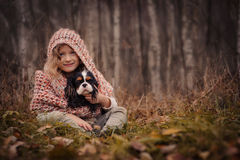 Cute happy kid girl with her dog on cozy autumn walk in forest Royalty Free Stock Photos